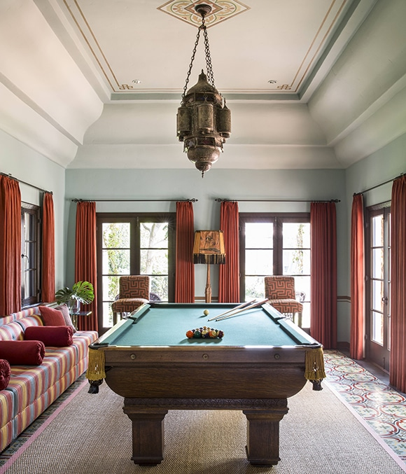 Billiard room looking at pool table, windows and seating area.