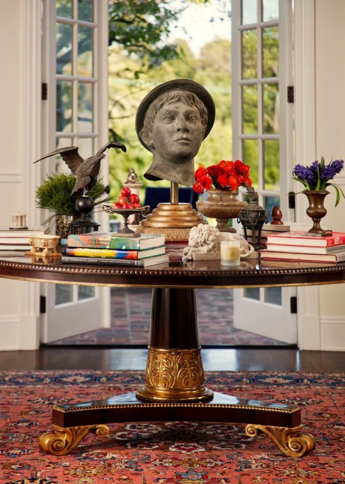 Foyer with a bust on the center table, designed by Timothy Corrigan