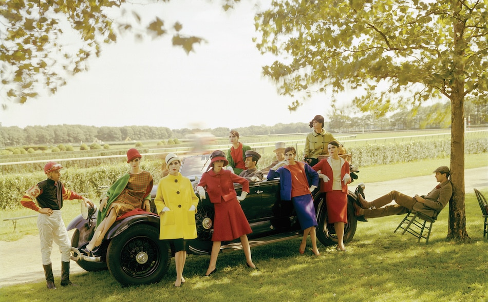 Models in Norman Norell sporty daytime outfits in vivid fall hues, shot at the Belmont Racetrack in 1960.